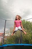 stock photo of bounce house  - Small cute child jumping on trampoline  - JPG