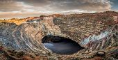 stock photo of open-pit mine  - Panoramic an open pit mine with lake in the center - JPG