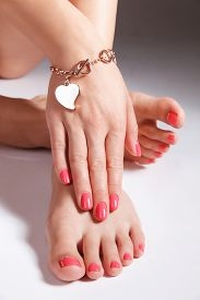 stock photo of painted toes  - Manicured and pedicured gel polished nails and toes - JPG