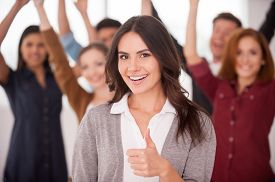 picture of stand up  - Beautiful young woman showing her thumb up and smiling while group of happy young people standing on background and keeping arms - JPG