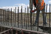 foto of concrete pouring  - Building construction worker pouring cement or concrete with pump tube - JPG