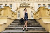 picture of palace  - smiling elegant pretty girl in blue dress with hat standing outside stairs of old fashion palace posing - JPG