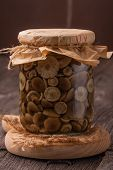 picture of marinade  - Marinaded mushrooms in a glass jar on wooden table - JPG