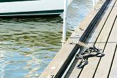 image of marina  - Small rope curled up on wooden bridge on marina - JPG