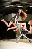 picture of trolley  - Two young beautiful playful fashionable girls in dresses with shopping trolley indoor on store backdrop vertical picture - JPG