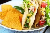 picture of tacos  - Tasty taco with nachos chips  and vegetables on plate close up - JPG