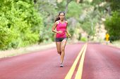 Running fit woman - female runner training outdoors jogging on red road in amazing landscape nature. poster