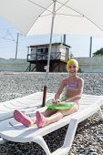 image of bathing  - girl in a bathing cap on a lounger on the beach - JPG