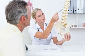 stock photo of spine  - Doctor showing her patient a spine model in medical office - JPG