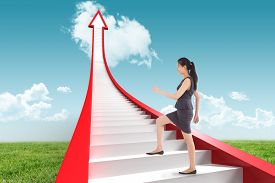 foto of step-up  - Businesswoman stepping up against blue sky over green field - JPG