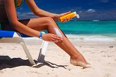 picture of woman body  - Tan woman applying sun protection lotion - JPG