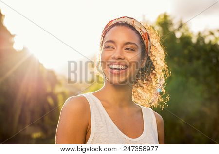 poster of Portrait of beautiful african american woman smiling and looking away at park during sunset. Outdoor