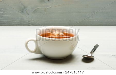 poster of Mug Filled With Boiling Water, Teabag And Spoon On White Background. Mug Filled With Hot Water And D