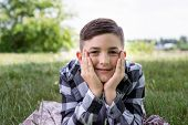 Close-up Portrait Of Happy Young Boy In Plaid Shirt Relaxing On Fresh Grass In Park. Cheerful Child  poster