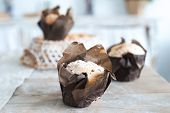 Freshly Baked Cupcakes Muffins On A Large Textured Wooden Table. Home-made Pastries In Parchment Pap poster