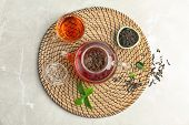 Teapot With Hot Aromatic Tea, Dry And Fresh Leaves On Wicker Mat, Top View poster