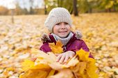 childhood, season and people concept - happy little girl with fallen maple leaves at autumn park poster