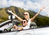 road trip, technology and travel concept - happy couple driving in convertible car and taking pictur poster