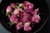 Buds Of Pink Faded Dry Roses For A Rose Bud Tea In A Black Cup On A Black Slate Background (flat Lay poster