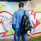 A Young Graffiti Artist With A Black Bag Looks At The Wall With His Graffiti On A Wall. Street Art C poster