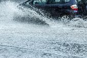Car Moving With High Speed Through Water Puddle On Flooded City Road During Heavy Rain poster