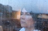 Woman Looking Out The Window On A Rainy Day poster