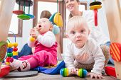 Cute baby girl showing progress and curiosity by trying to reach multicolored wooden toys, while sit poster