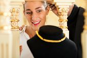 image of collier  - Woman at the jeweller is looking for jewellery - JPG