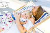 Portrait Of Dorable Blondy Baby Girl In Dress Laying On Her Mother Sitting, In The Deckchair In The  poster