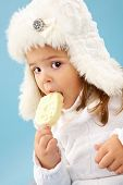 Little girl in white furry hat looking at camera while eating ice-cream poster
