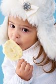 Little girl in white furry hat eating delicious ice-cream poster