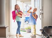 Pupils of primary school. Girls with backpack is going to school from home. Beginning of lessons. Fi poster