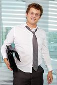 stock photo of untidiness  - Sloppy businessman with briefcase looking at camera - JPG