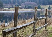 pic of split rail fence  - This nature landscape is a wet wood split rail fence near a small lake with evergreen trees in the background - JPG