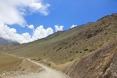 Dirt Road In The Mountains Of Nepal On A Background Of Blue Sky And Beautiful Clouds poster