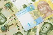 A Blue And Yellow One Ukrainian Hryvnia Bank Note On A Bed Of Chinese One Yuan Bank Notes poster