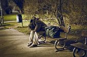 stock photo of tramp  - homeless man sitting on a bench in a park - JPG