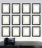 Twelve framed award certificates for employee of the month images on a wall in an office, in front o