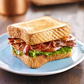 stock photo of bacon  - BLT bacon lettuce tomato sandwich on blue plate - JPG