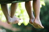 image of barefoot  - Happy children sitting on green grass outdoors in summer park - JPG