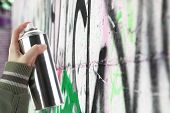 stock photo of spray can  - Human hand holding a graffiti Spray can in front of a colorful wall - JPG