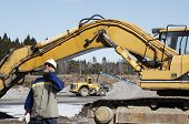 stock photo of jcb  - building worker directing bulldozers and trucks inside industrial area - JPG