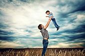 picture of cloudy  - Happy father playing with his little son in the wheat field over beautiful cloudy sky - JPG