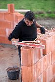 stock photo of erection  - bricklayer erecting red brick wall - JPG