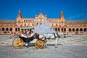 SEVILLE, SPAIN-SEP 10: Tourists enjoy a trip on horsedrawn cart on Plaza de Espana, Seville on Sep 1