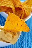 closeup of a bowl with tortilla chips dipped in nacho cheese on a blue background