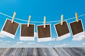 picture of polaroid  - Old polaroid film blanks hanging on a rope held by clothespins - JPG