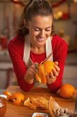 stock photo of orange peel  - Happy young housewife removing orange peel in kitchen - JPG