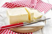 stock photo of margarine  - Butter on a chopping board on a table with knife - JPG