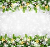 picture of conifers  - Christmas border of fir twigs decorated with stars snow and cones on light gray background with falling snowflakes - JPG